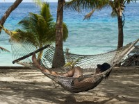 Man relaxing in a hammock strung between palm trees overlooking the ocean at a tropical island resort